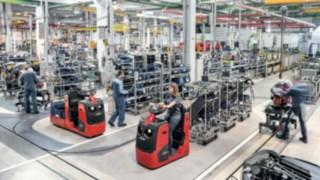 Schlepper mit mehreren Warenträgern transportieren Bauteile an die Produktionslinie.
