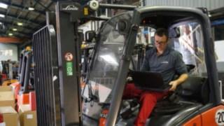 Techniker mit Laotop beim der Inspektion eines Staplers zur Aufbereitung